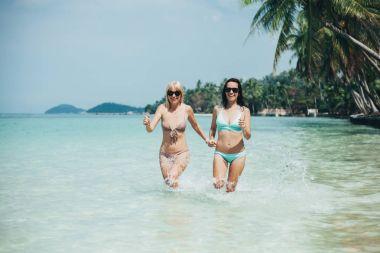 Happy girls in swimsuits in ocean on tropical resort stock vector