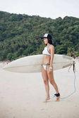 beautiful girl in cap and bikini holding surfboard on sandy beach