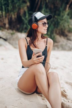 Young beautiful woman listening music with headphones at tropical beach stock vector