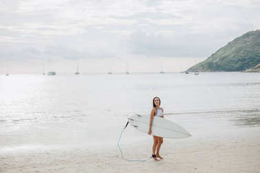 young surfer in swimsuit walking with surfboard on beach at sea