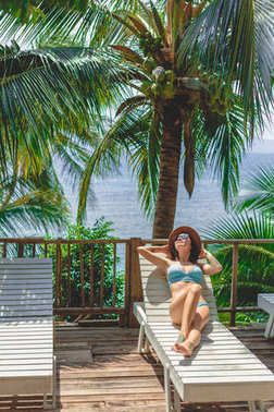 Beautiful girl lying in bikini and hat on lounge chair at tropical resort stock vector