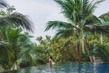 Girl in bikini lying in swimming pool with beautiful nature around stock vector