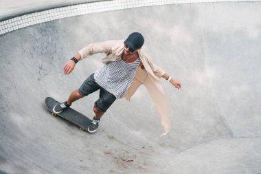 Young skater skating on longboard in pool at skatepark stock vector