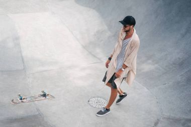 Handsome skater looking at falling skate stock vector