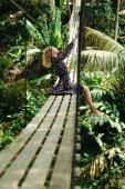 Seitenansicht attraktiver Frau, die auf Hängebrücke im Dschungel posiert