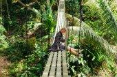 donna attraente sorridente che si siede sulla passerella di legno nella giungla