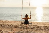 Photo back view of woman on swing at ocean beach during sunset