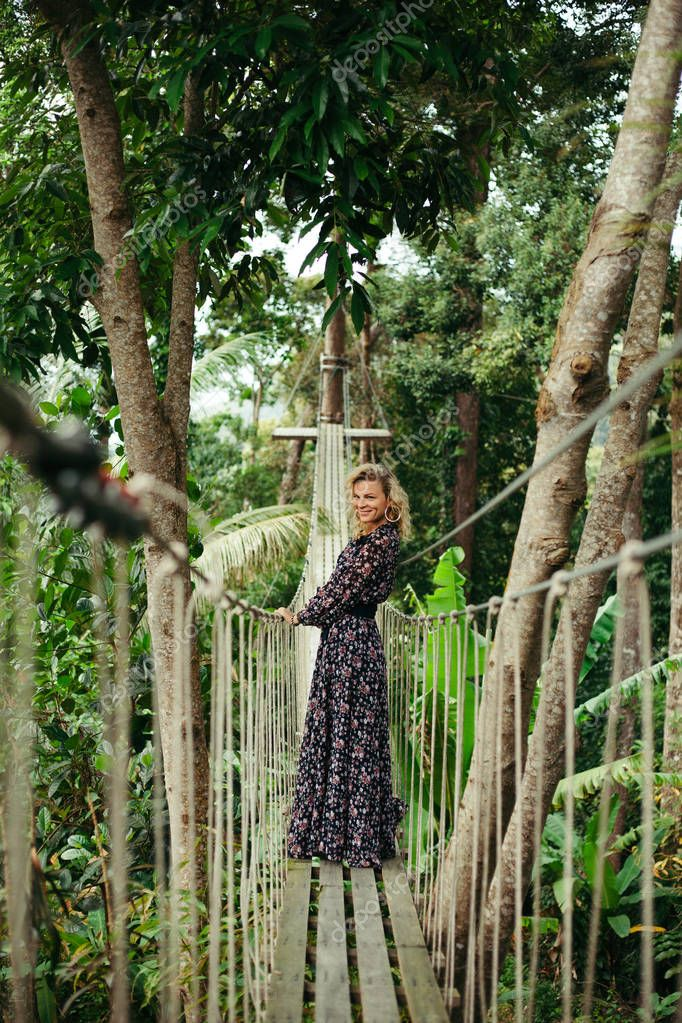 smiling attractive woman standing on footbridge in jungle and looking away