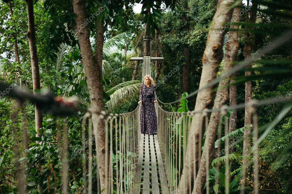 attractive serious woman in dress standing on footbridge in jungle