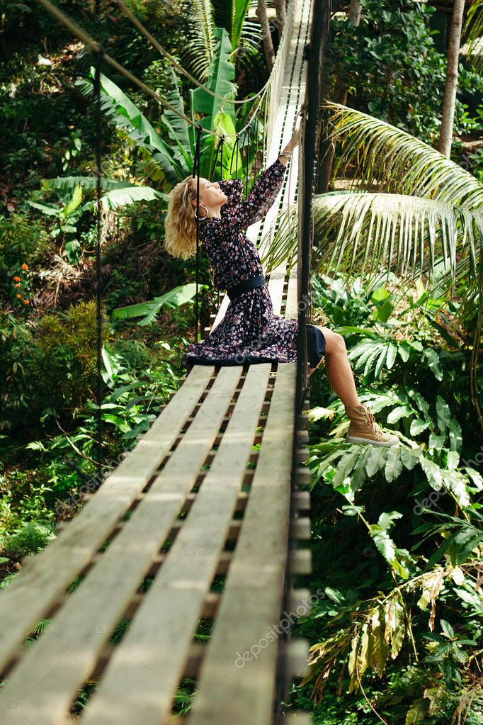 side view of attractive woman posing on suspension bridge in jungle