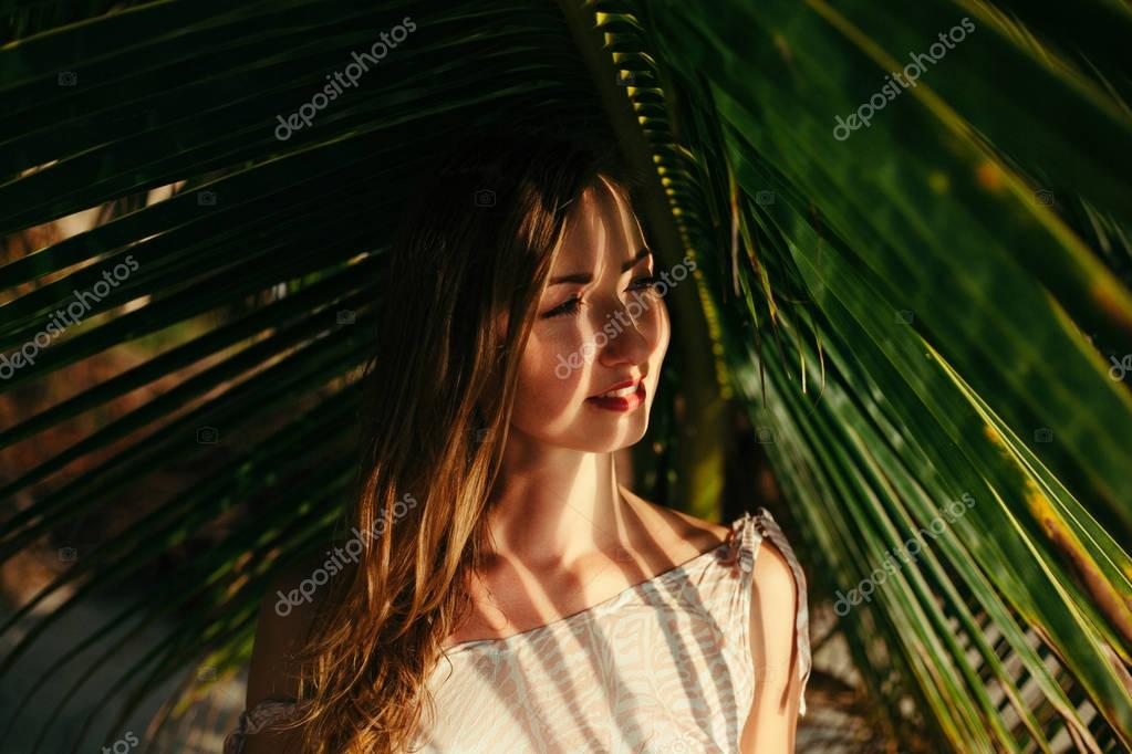 portrait of attractive girl under big green palm tree leaf