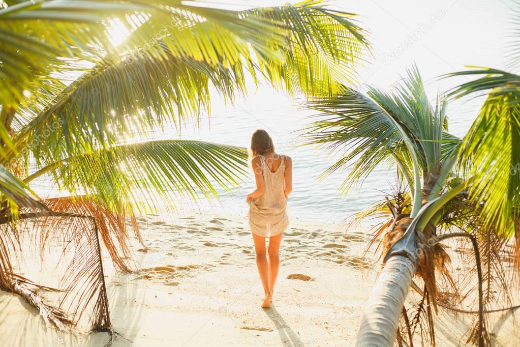 rear view of woman standing between palm trees on sea beach