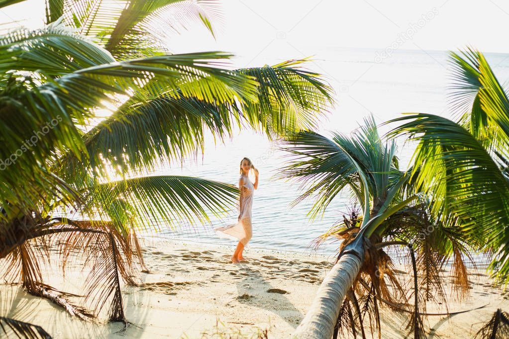 beautiful woman posing between palm trees on ocean beach
