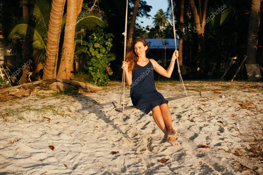 smiling beautiful woman on swing between palm trees looking at camera at beach