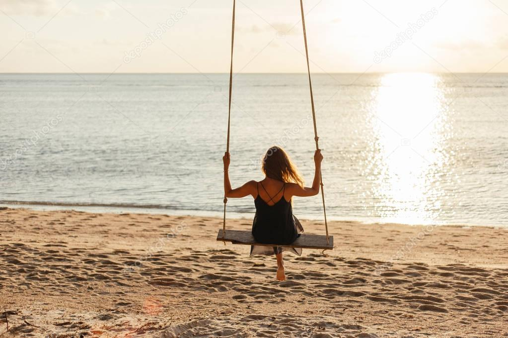 back view of woman on swing at ocean beach during sunset