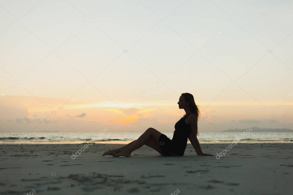 silhouette of woman sitting on ocean sandy beach during sunset