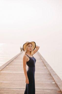 beautiful sensual woman in hat and dress looking at camera near ocean
