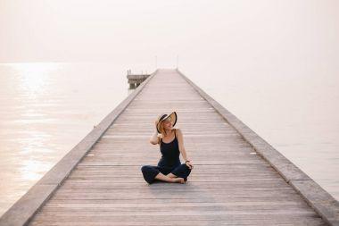 happy beautiful woman in hat sitting on pier near ocean