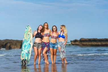 Group of attractive women in bikini with surfboard posing in front of ocean stock vector