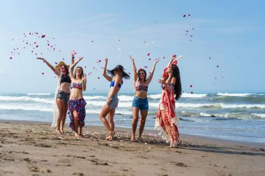 Group of happy young women throwing up petals on beach stock vector