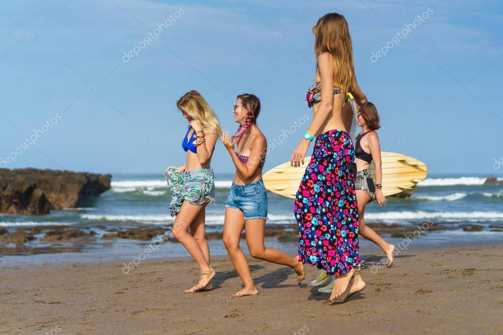 beautiful women with surfboard walking by beach