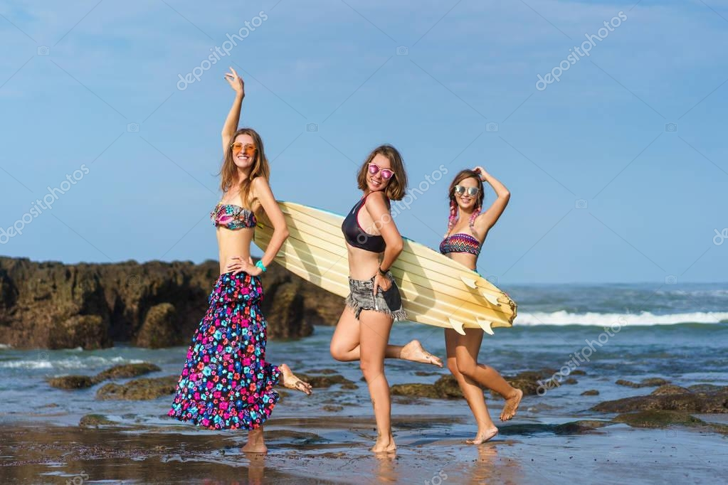 group of happy young women with surfboard on beach
