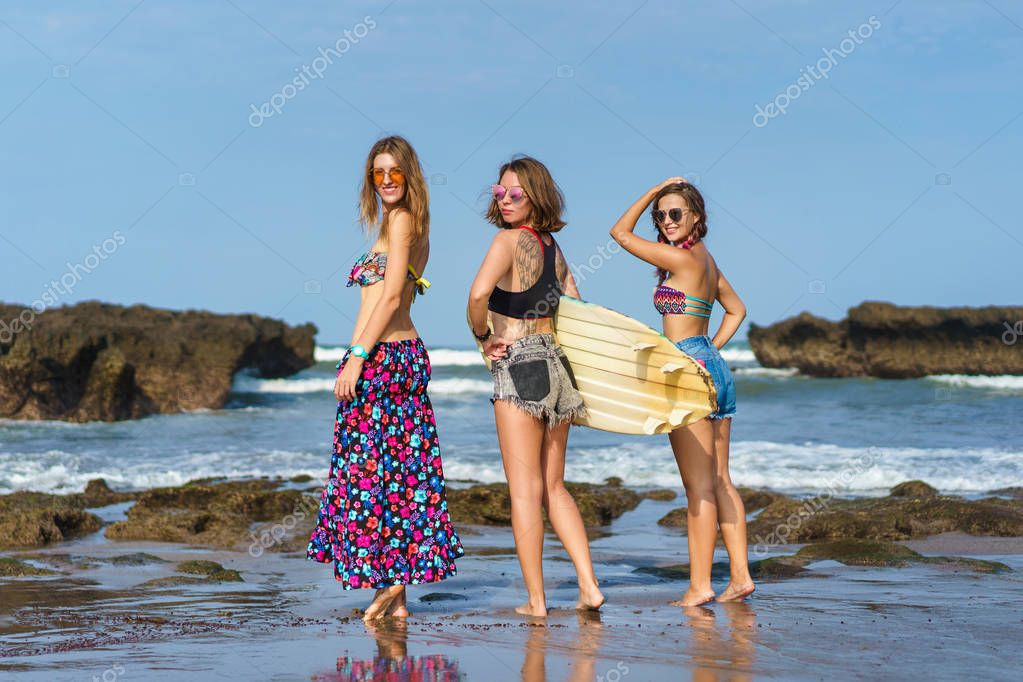 group of attractive young women with surfboard on beach