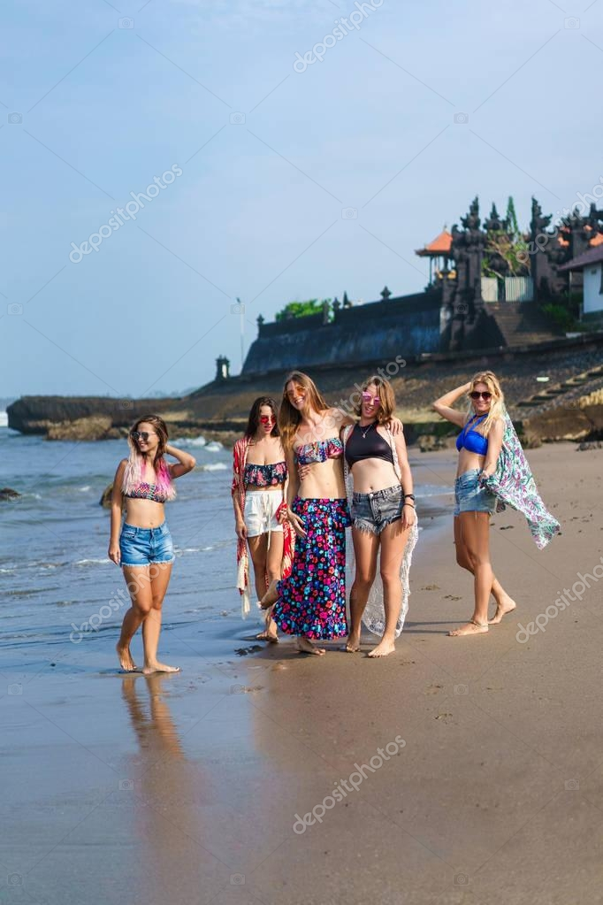 group of stylish young women in bikini posing on beach