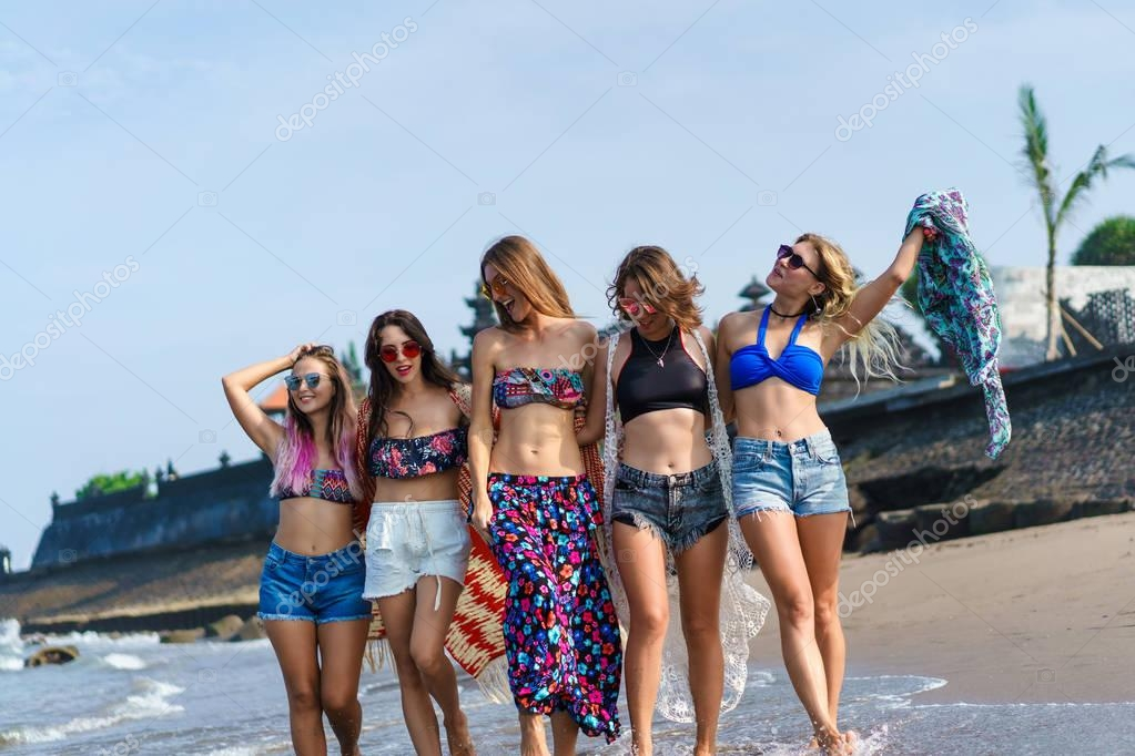 group of attractive young women in bikini spending time together on beach