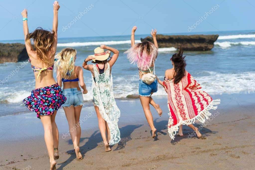 rear view of group of young women running at sea