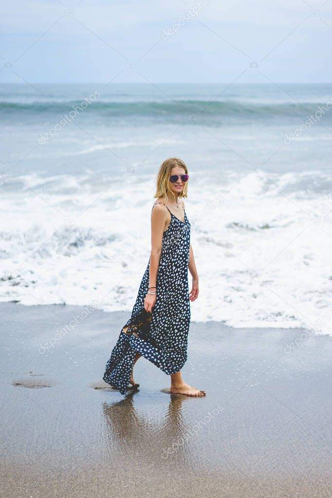 beautiful blonde girl in long dress walking near ocean