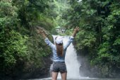 Photo back view of woman with outstretched arms with Aling-Aling Waterfall on background, Bali, Indonesia