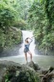 Fotografie Žena stojící na skále s Aling Aling vodopád a zelené rostliny na pozadí, Bali, Indonésie