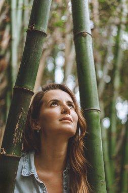 Portrait of beautiful pensive woman standing among bamboo plants, Bali, Indonesia stock vector