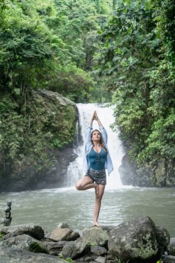 attractive woman practicing yoga with Aling-Aling waterfall on backdrop, Bali, Indonesia