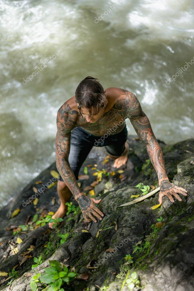 overhead view of tattooed man climbing on rocks with river on background, Bali, Indonesia