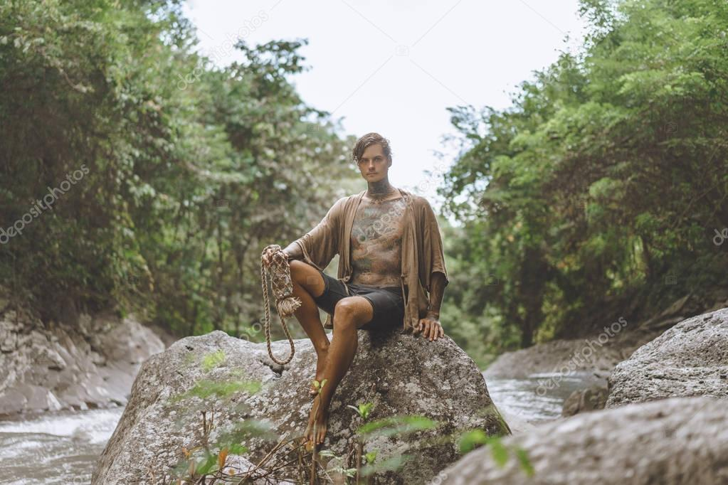 tattooed man with water bottle resting on rock with green plants and river on backdrop, Bali, Indonesia