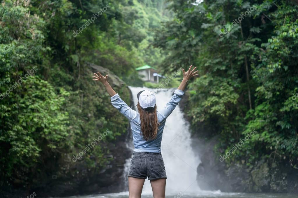 back view of woman with outstretched arms with Aling-Aling Waterfall on background, Bali, Indonesia