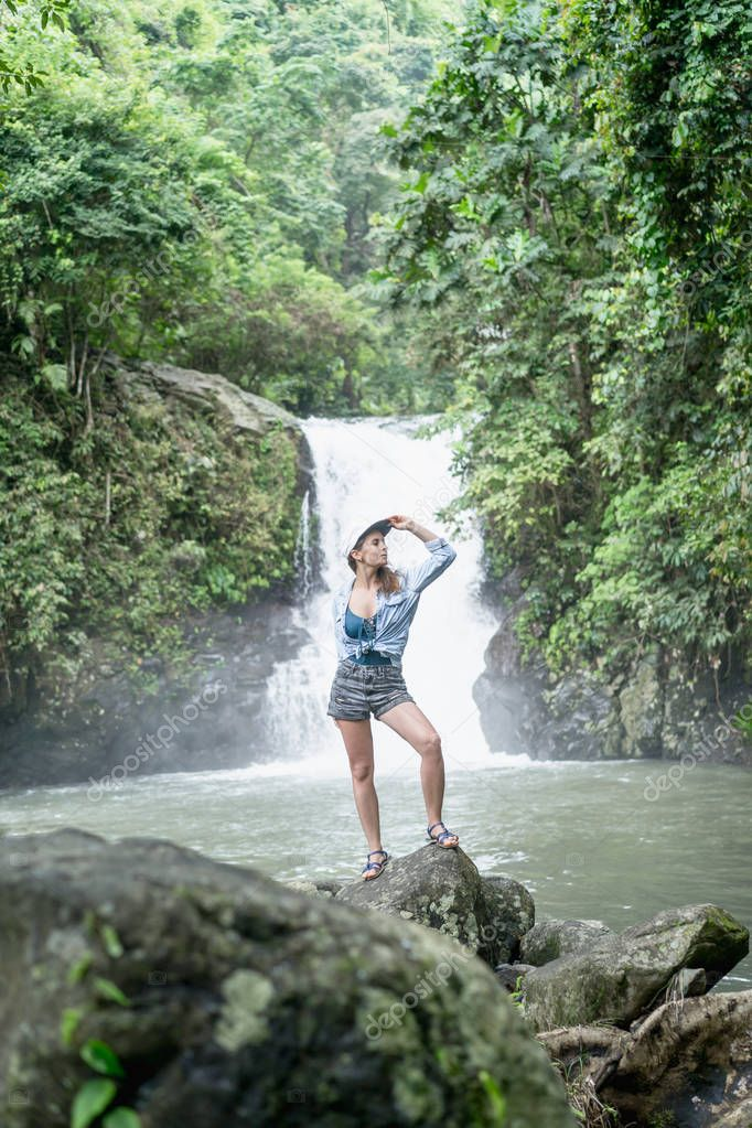 woman standing on rock with Aling-Aling waterfall and green plants on background, Bali, Indonesia