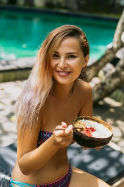 beautiful young woman in bikini eating tropical dessert and smiling at camera