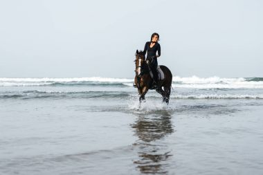front view of young woman riding horse in wavy water