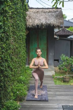 beautiful young woman practicing yoga in Warrior I with Prayer Hands pose in garden