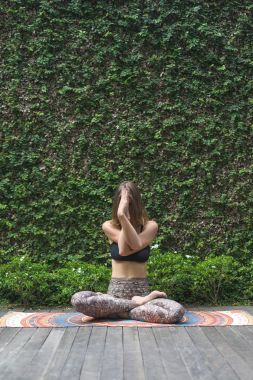 beautiful young woman practicing yoga in lotus pose in front of wall covered with green leaves