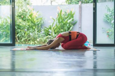 side view of young woman practicing yoga in Extended Child (Utthita Balasana) pose
