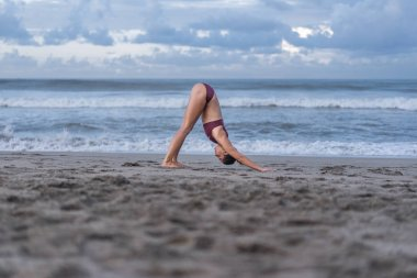 side view of attractive young woman practicing yoga in Downward-Facing Dog pose (Adho Mukha Svanasana) on seashore