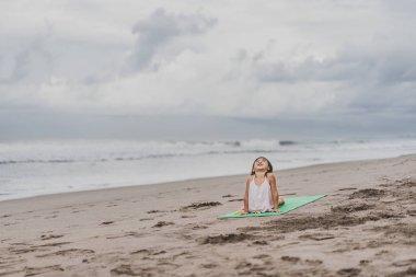 happy little child practicing yoga in Upward-Facing Dog (Urdhva Mukha Svanasana) pose on seashore