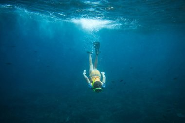 underwater photo of woman in fins, diving mask and snorkel diving alone in ocean