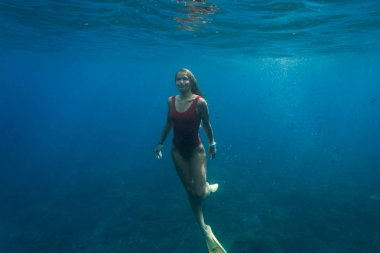 underwater photo of young woman in swimming suit and fins diving in ocean alone