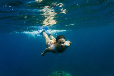underwater photo of young woman in swimming suit diving in ocean alone