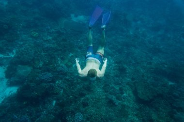 underwater photo of young man in flippers diving in ocean alone